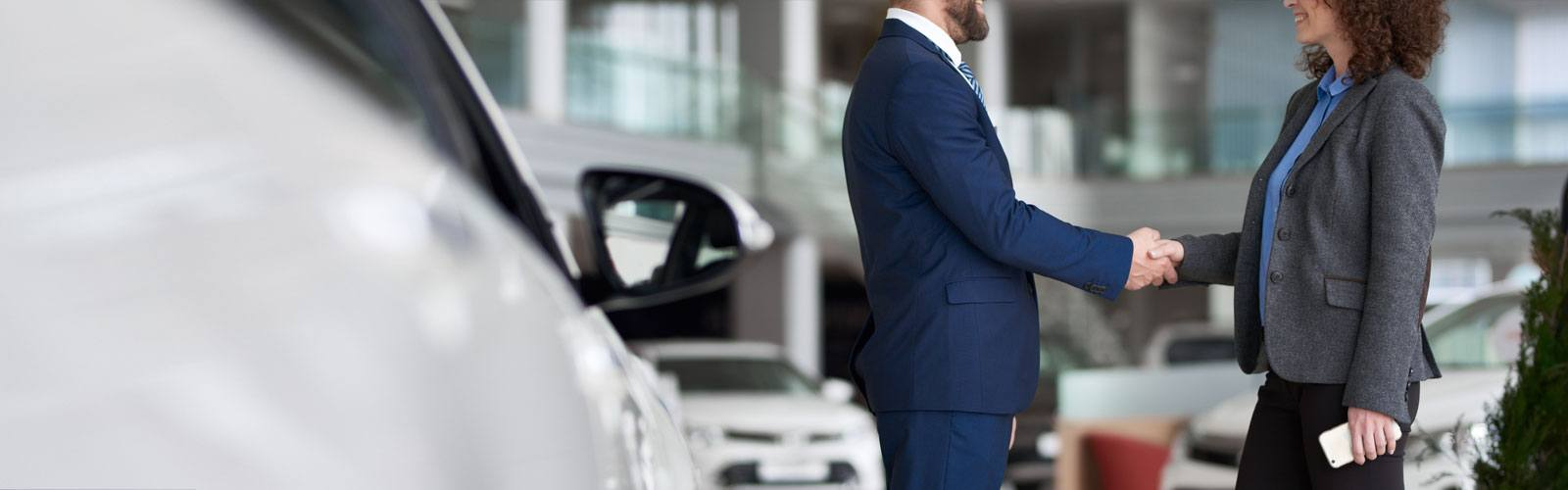 Woman shaking hands with an auto dealer.