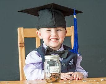 A little kid collecting coins in a graduation cap.