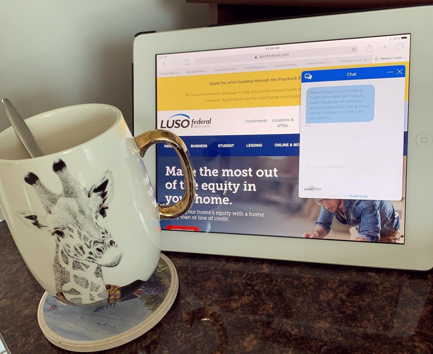 Coffee Cup next to ipad displaying luso website with Live Chat popup