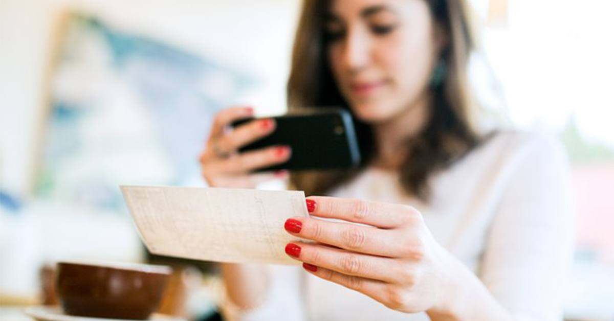 Woman holding check and cell phone