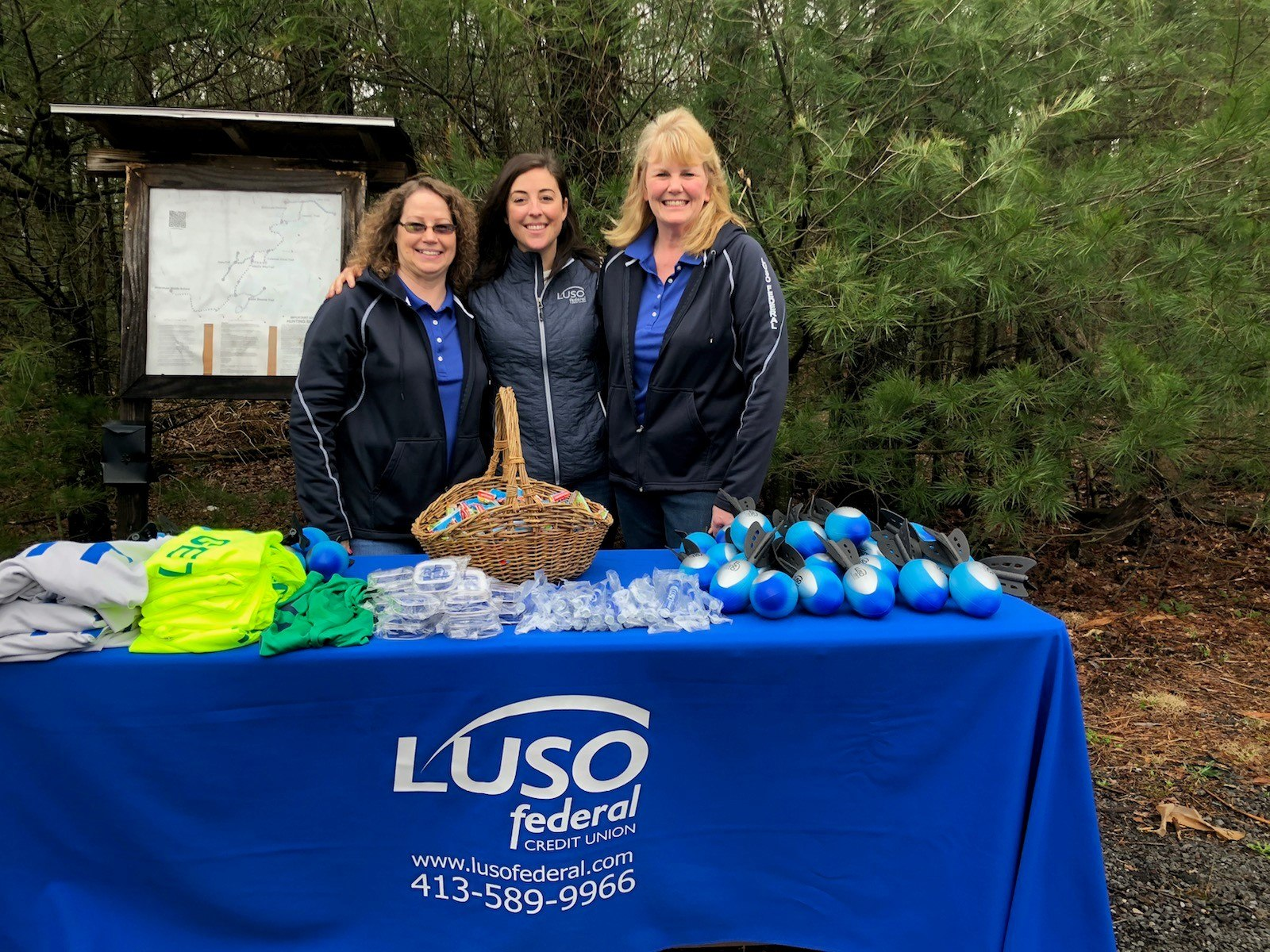 Three LUSO women standing behind LUSO table